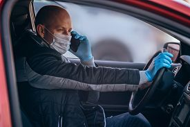 A Man Driving A Car In Protective Medical Mask And Gloves Is Talking On Phone. Safe Drive In A Taxi