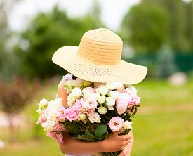 The Girl Holds A Large Bouquet Of Pink And White Peonies In Front Of Her. A Child In A Straw Hat Wit