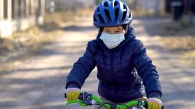 A Child On A Walk During The Quarantine Period Of The Coronavirus Covid19. The Boy Rides A Bicycle I