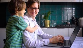 Young Man Working In The Kitchen At A Laptop With His A Son. Home Office With Kids. Concept For Remo