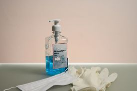 Bottle Of Clear Liquid Antibacterial Hand Gel. Antibacterial Hand Sanitizer, Medical Gloves And Mask