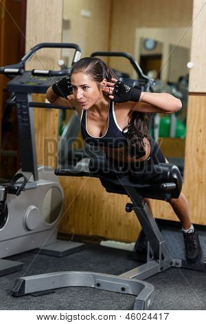 Sports young woman doing exercises on trainer back machine in the gym. Fitness. poster