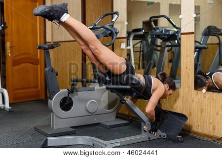 Sports young woman doing exercises on trainer back machine in the gym. Reverse Hyperextension. poster