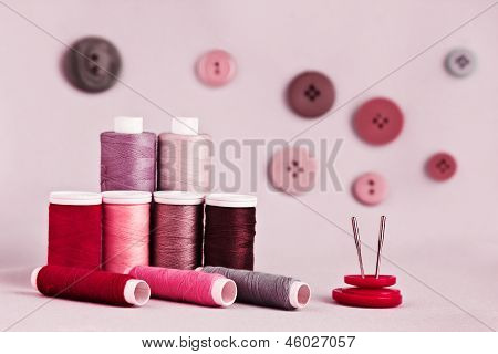 Sewing kit with buttons on pink background
