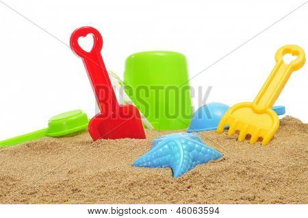 closeup of some beach toys, as a starfish-shaped sand mold, and shovels and rakes of different colors, on the sand of a beach or of a sandpit