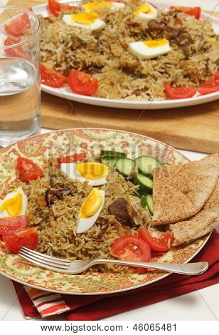 A homemade traditional Indian beef biryani, served with hard-boiled eggs, tomato and cucumber, with flat bread and a glass of water, and the serving dish in the background poster