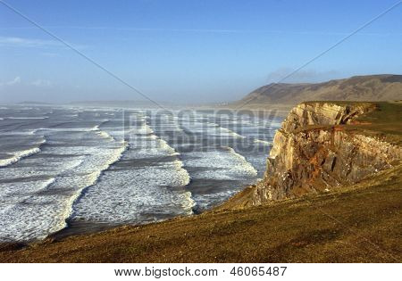 Lines of surf roll in to Rhossili Beach (or Llangenneth Sands), on the Gower Peninsula in South Wales, UK. The three-mile wide beach is the largest of many popular surfing locations on the peninsula.