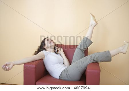 Happy woman talking on phone while sitting in chair
