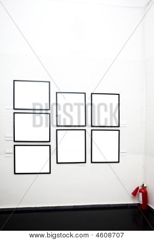 poster of white walls in museum with empty frames