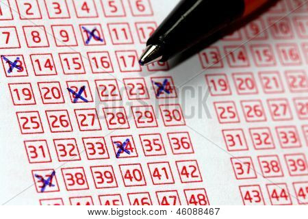 Pen and lucky numbers marked on a lottery coupon shallow depth of field. poster