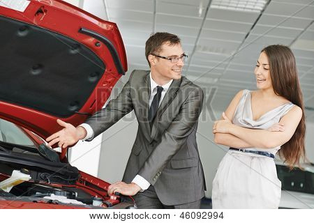 Car salesperson demonstrating new automobile to young woman