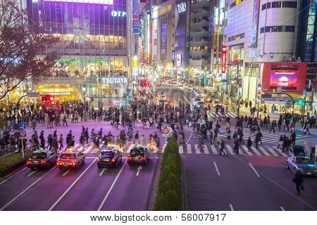 TOKYO - DECEMBER 10: Pedestrians cross at Shibuya Crossing on December 10, 2013 in Tokyo, Japan. The crosswalk is one of the world's most famous implementations of a scramble crosswalk.