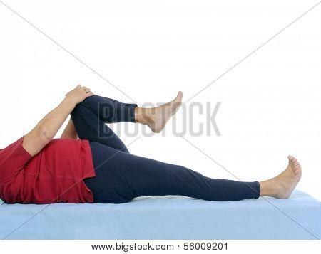 Older patient performing funtional test of hip joint contraction lying on bed