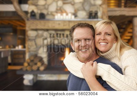 Happy Affectionate Couple at Rustic Fireplace in Log Cabin.