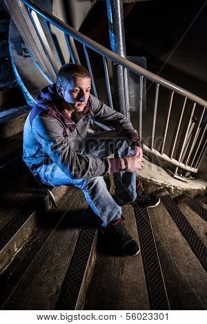Young Man Sitting On Urban Stairs At Night