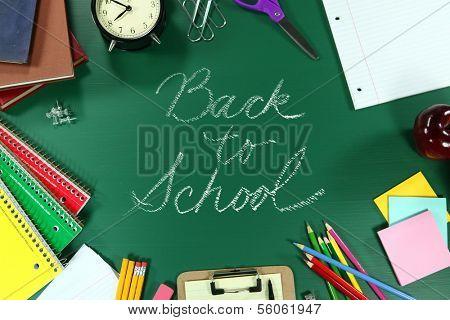 Back to School Supplies on Green Chalkboard Background