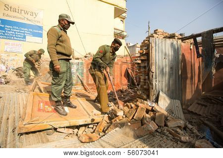 KATHMANDU, NEPAL - DEC 24: Unknown nepalese police during an operation on demolition of residential slums, Dec 24, 2013 in Kathmandu, Nepal. In KTM is home to 50,000 squatters spread across city slums.