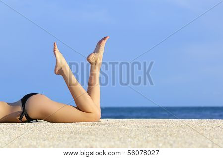 Beautiful Smooth Model Legs Resting On The Sand Of The Beach