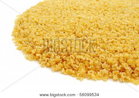 a pile of uncooked alphabet pasta on a white background