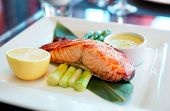 Salmon steak cooked in asian style on restaurant table poster