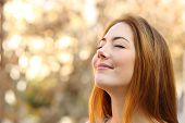 Portrait of a beautiful woman doing breath exercises with an autumn unfocused background poster