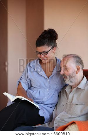 young person reading book to elderly man poster