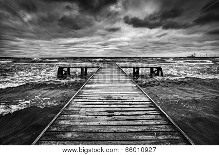 Old wooden jetty, pier, during storm on the sea. Dramatic sky with dark, heavy clouds. Black and white