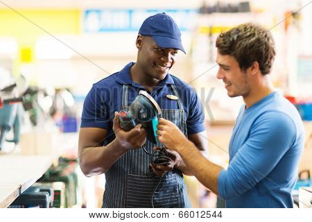 friendly hardware store worker showing customer a sander