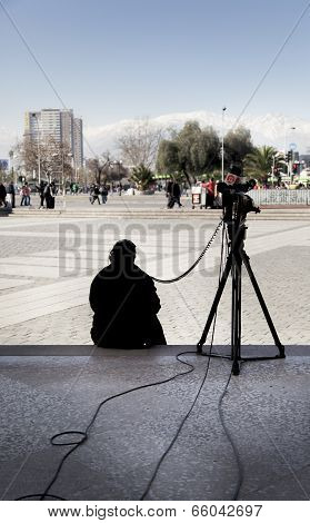 Rear view of a photographer sitting with his camera, Santiago, Chile