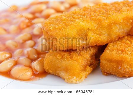 Plate of baked beans with fried fishfingers.
