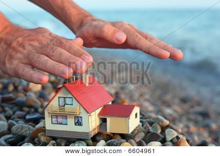 Model Of House With Garage On Stony Beach In Evening, Man's Hands Over House