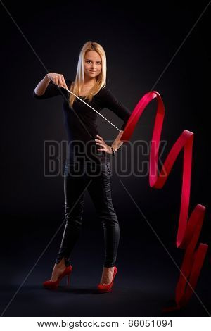 Pretty rhytmic gymnast exercising with ribbon over black background.