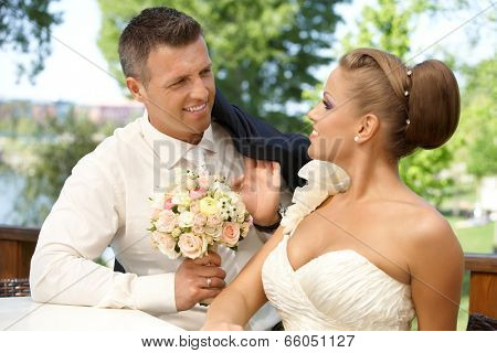 Young couple smiling happy on wedding-day outdoors, looking at each other with love.