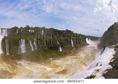 Raging and roaring water in the Brazilian side of the Iguazu Falls.  Turbid yellow-brown waves flow down