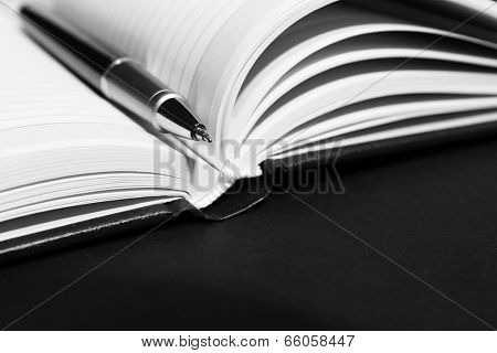 Pen on opened book on black table, close up