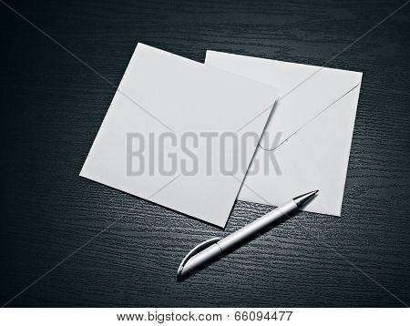 White envelope letter and white pen on black table