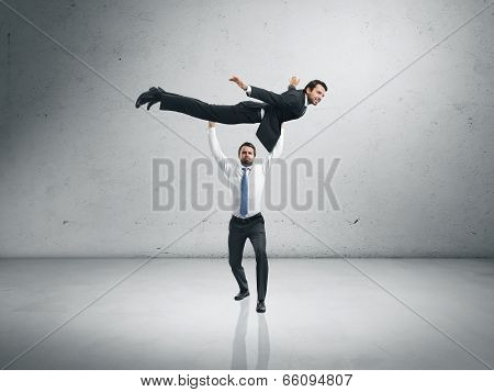 One businessman lifting the second one and helping him to fly. Team work concept.