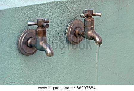 Two Rusty Old Taps  With Water Flowing From One