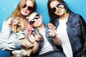 happy two sisters and brother with yorkshire terrier poster