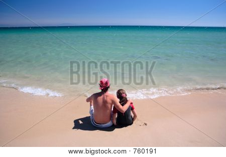 Man And Daughter Sitting On Sunny Deserted Beach