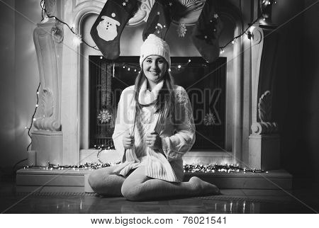 Monochrome Photo Of Smiling Woman Sitting On Floor Next To Fireplace