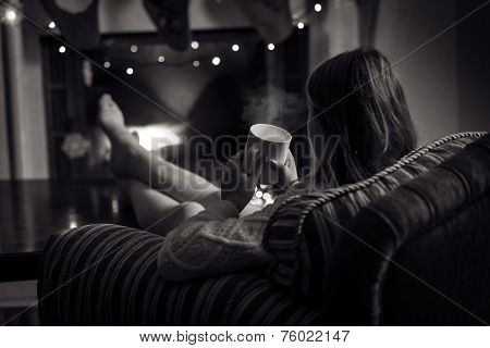 Monochrome Photo Of Cute Woman Sitting At Fireplace With Cup Of Tea