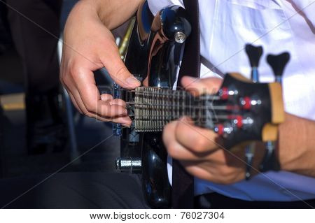 Musician playing bass guitar focus on right hand