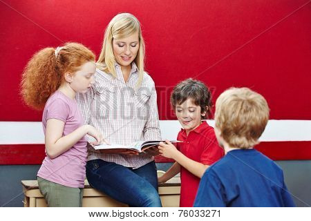 Students and teacher reading book in elementary school