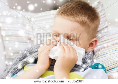 childhood, healthcare and people concept - ill boy with flu blowing nose into tissue at home