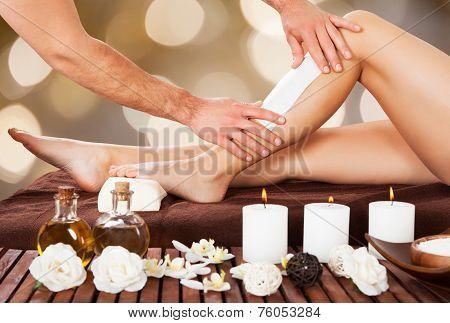 Male Beautician Waxing Woman's Leg In Spa