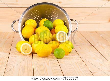 Composition of metal colander and lemons.