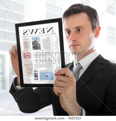 Businessman Holding A Touchpad Pc, Reading A Newspaper