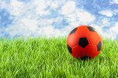 orange Soccer ball on grass against blue cloudy sky poster
