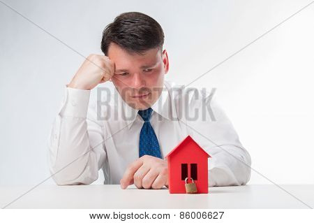 Sad Man with a red paper house